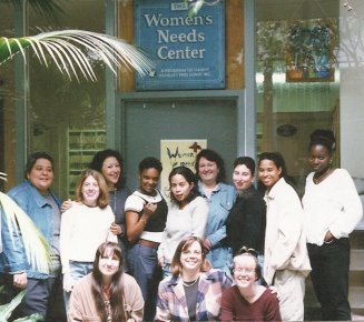 "Group color photo of a diverse group of women in casual wear in front of a door with a sign that reads, ""Women's Needs Center.'"