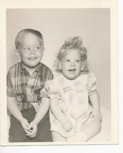B/w photo of a little boy and younger girl sitting. Both smile and the boy is giving the girl a mischievous sideways glance.