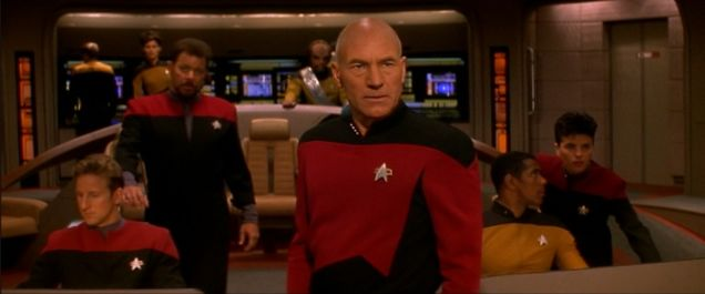 Captain Picard on the bridge looking toward the screen.