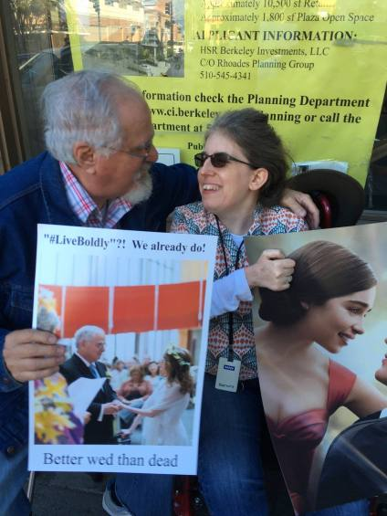 Color photo of a sitting white couple, man and woman, smiling at each other holding protest signs.