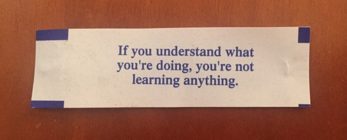 Color photo of a fortune cookie that reads,