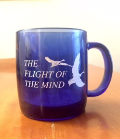 A cobalt blue glass mug with 2 white birds in flight and The Flight of the Mind