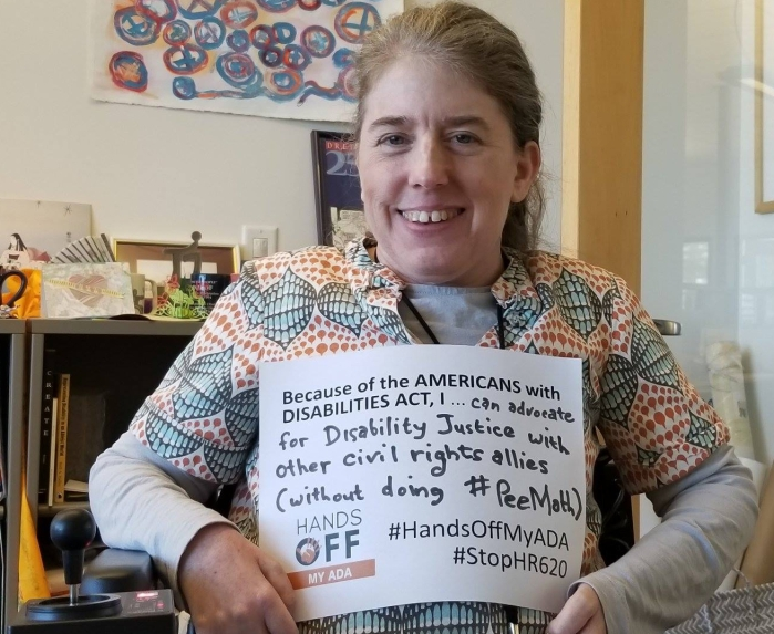 "Color photo of Ingrid Tischer, a middle-aged white cis woman, sitting in her wheelchair and smiling, golding a sign, ""Because of the Americans with Disabilities Act, I...can advocate for Disability Justice with other civilrights allies (without doing #PeeMath). #HandsOffMyADA #StopHR620"