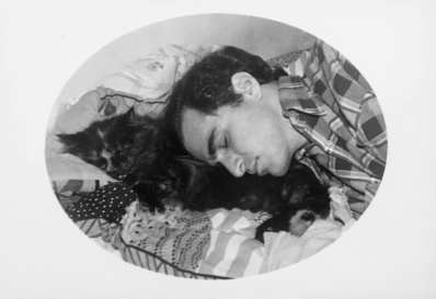 B/W photo of a young white man sleeping peacefully with a calico kitty