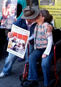 Ken Stein and Ingrid Tischer, organizers of the protest, kiss, holding a poster with a photograph of their wedding.